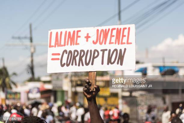People hold up signs during a demonstration on February 14, 2021 in Port-au-Prince. - Several thousand people demonstrated on February 14, 2021 in...