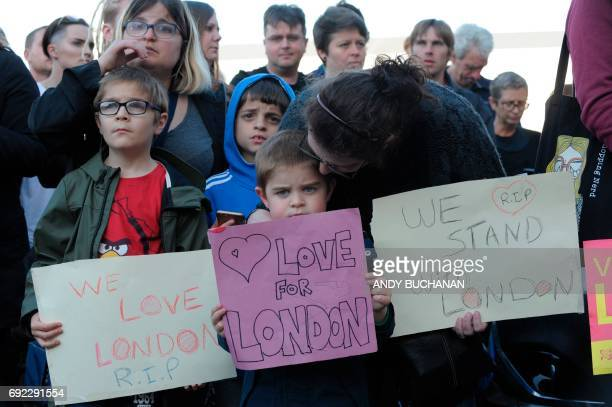 People hold up signs in solidarty with victims of the London terror attack outside the County Hotel in Carlisle Cumbria on June 4 2017 where...