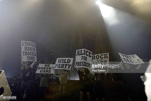 People hold up signs on the stage during a performance by heavy metal musician Alice Cooper at the Sears Centre in Hoffman Estates, Illinois,...