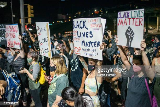 People hold up signs outside Austin Police Department after a vigil for Garrett Foster on July 26, 2020 in downtown Austin, Texas. Garrett Foster who...