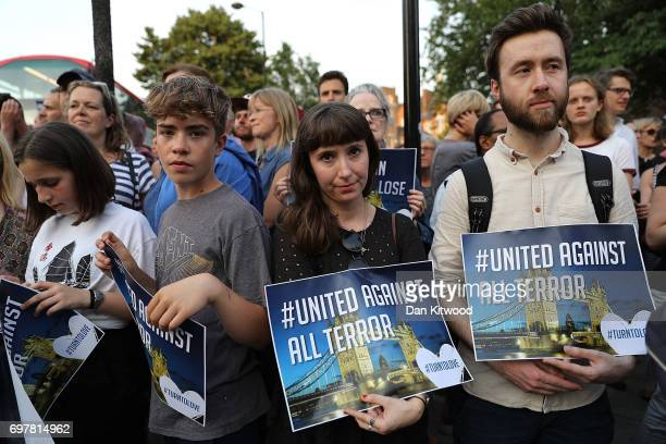 People hold up signs saying 'united against terror' as they attend a vigil outside Finsbury Park Mosque on June 19 2017 in London England Worshippers...