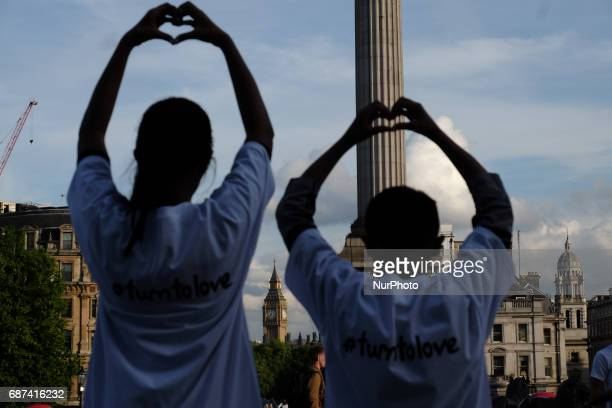 People hold up signs which say 'Turn to Love for Manchester' during a vigil for the victims of yesterday's Manchester Arena terror attack in...