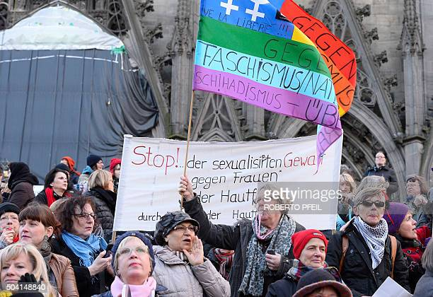 People hold up signs while taking part in a demonstration against violence against women in front of the cathedral in Cologne western Germany on...