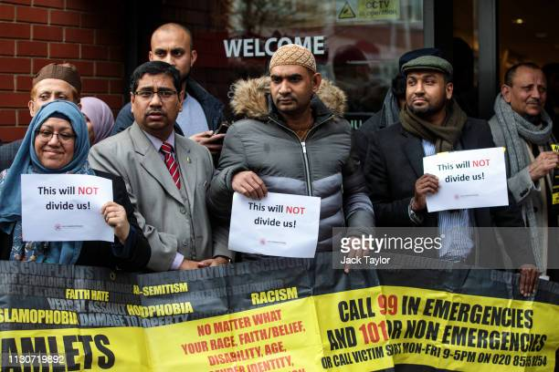 People hold up signs with the words 'This will not divide us' as they attend a vigil at the East London Mosque for the victims of the New Zealand...