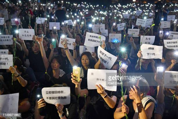People hold up smartphone lights and posters during a mums protest against alleged police brutality and the proposed extradition treaty near the...