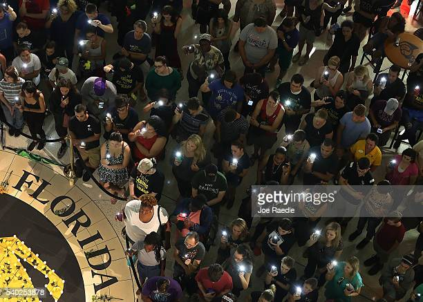 People hold up their cellphones instead of candles as names of those killed are read aloud during a memorial service at the University of Central...