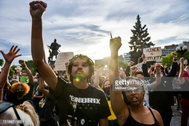 People hold up their fists on the steps of the Colorado State Capitol during the fourth consecutive day of protests in the aftermath of the death of...