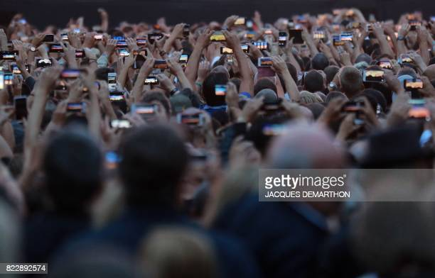 People hold up their mobile phones to film events on stage during a concert by Irish rock band U2 at the Stade de France in SaintDenis outside Paris...