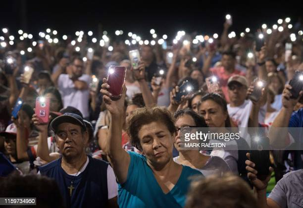 TOPSHOT People hold up their phones during a prayer and candle vigil organized by the city after a shooting left 20 people dead at the Cielo Vista...