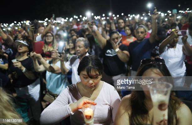 People hold up their phones in lieu of candles at an interfaith vigil for victims of a mass shooting, which left at least 20 people dead, on August...