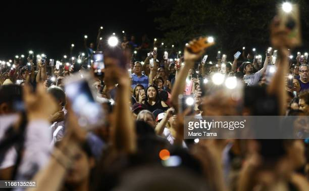 People hold up their phones in lieu of candles at an interfaith vigil for victims of a mass shooting which left at least 20 people dead on August 4...