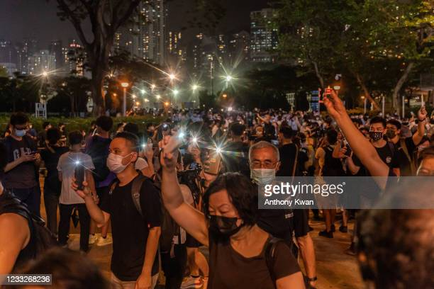 People hold up their phones with the light as they walk near the Victoria Park after police closed the venue where Hong Kong people traditionally...