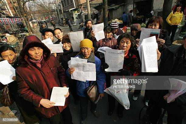 People hold up there petitions in a squatter village in southern Beijing 01 March 2005 where people from all over China have come to air their...