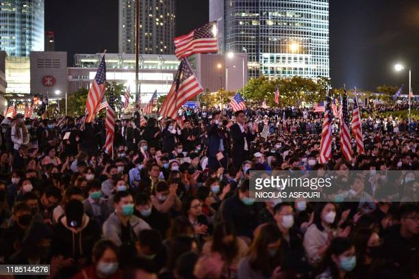 People hold up US national flags during a gathering of thanks at Edinburgh Place in Hong Kong's Central district on November 28 after US President...