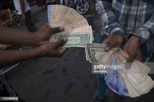 People hold U.S. Dollar and bolivar banknotes in the Catia neighborhood of Caracas, Venezuela, on Thursday, March 25, 2021. The serious side-business...
