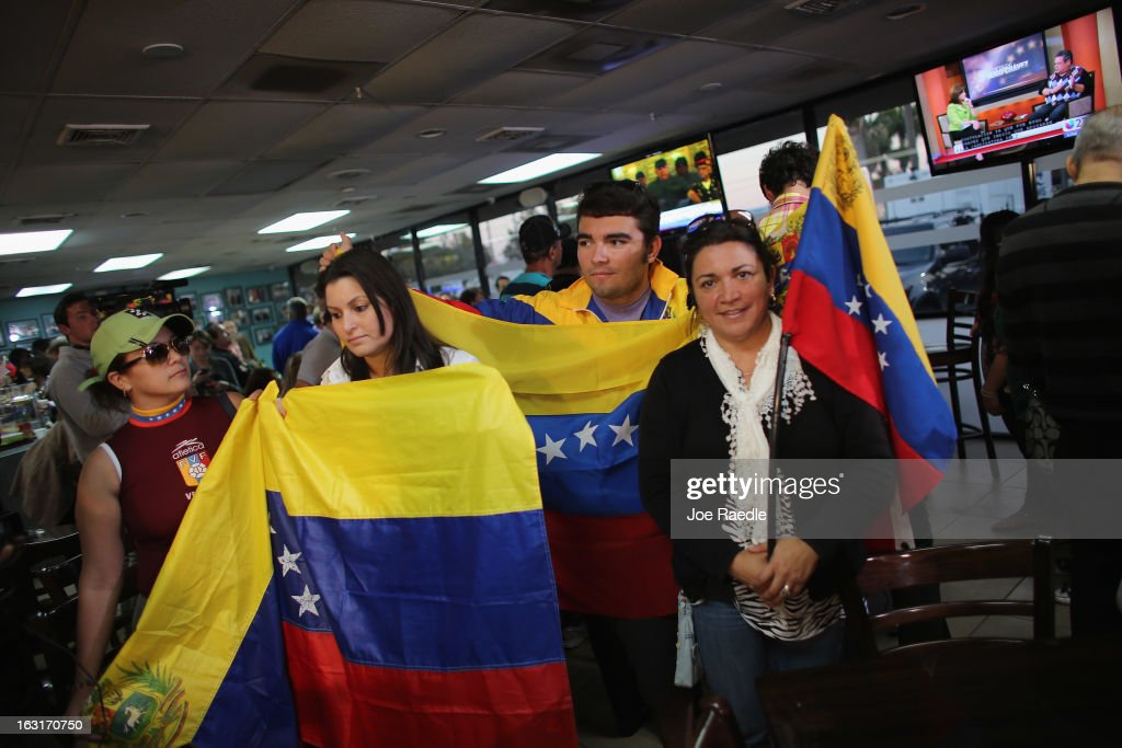 People hold Venezuelan flags as they listen to television sets reporting on the death of Venezuelan president Hugo Chavez, at El Arepazo 2 a restaurant in the heart of a neighborhood that has the largest concentration of Venezuelans in the U.S. on March 5, 2013 in Doral, Florida. The Venezuelan government announced today that Hugo Chavez lost his battle with cancer.