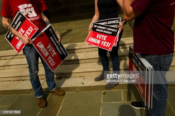 "People hold ""Vote Union Yes!"" signs during a protest in solidarity with Black Lives Matter, Stop Asian Hate and the unionization of Amazon.com, Inc...."