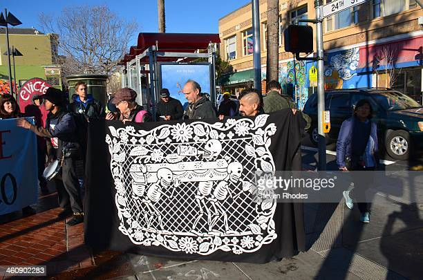 People holding a banner showing Day of the Dead skeletons on a funeral march after marching to the 24th and Mission BART station after blocking an...