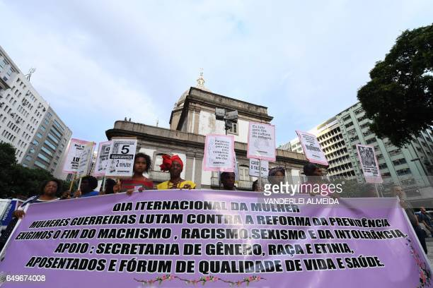 People holding a banner take part in the commemoration of the International Women's Day at Candelaria square in Rio de Janeiro Brazil on March 8 2017...