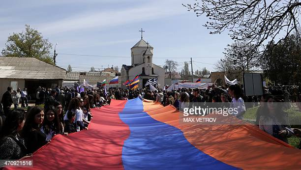 People holding a giant Armenian flag gather in Simferopol on April 24 2015 to mark the 100th anniversary of the Armenian genocide AFP PHOTO / MAX...