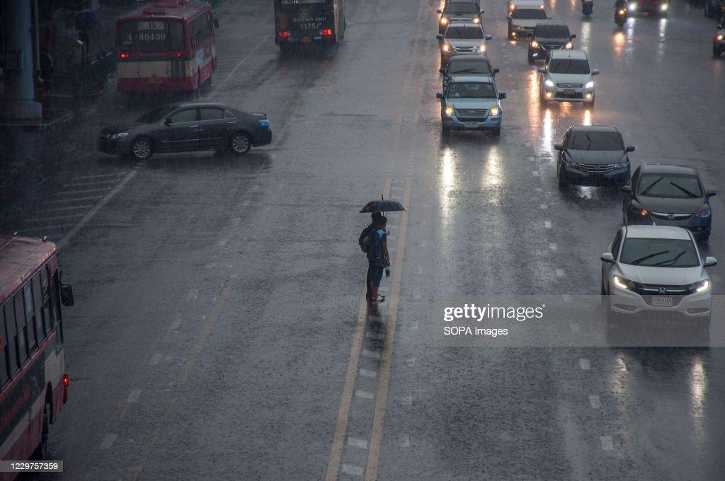 People holding an umbrella wait to cross Ratchadamri Road on... : ニュース写真