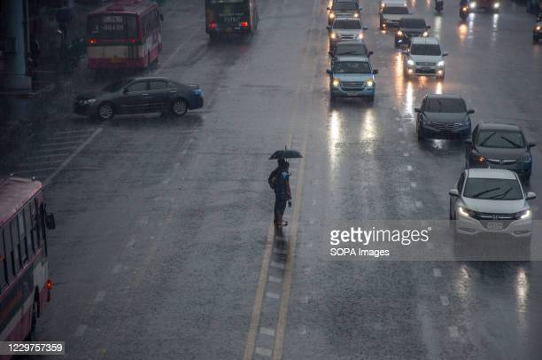 People holding an umbrella wait to cross Ratchadamri Road on a Rainy Day.