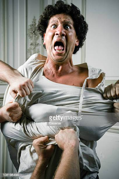 people holding angry young man in straight jacket - restraining stock photos and pictures