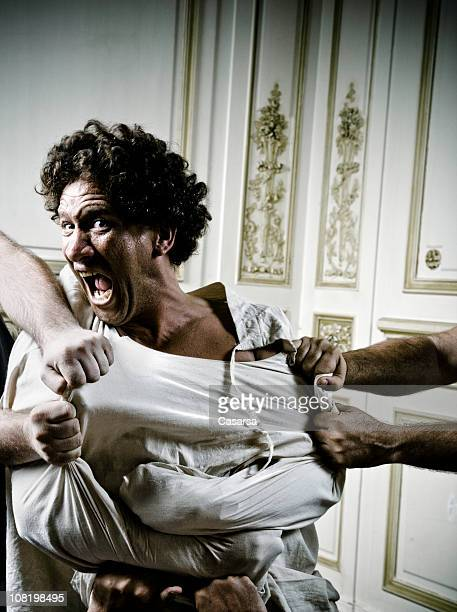 people holding angry young man in straight jacket - straight jacket stock pictures, royalty-free photos & images