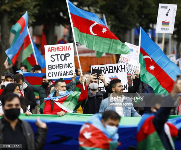 People holding Azerbaijan flags and banners gather to stage a protest against Armenia's cross-border attacks and to support Azerbaijan, at...