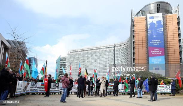 People holding Azerbaijani and Turkish flags gather at Schuman Square to protest Khojaly Massacre during its 25th anniversary in Brussels Belgium on...