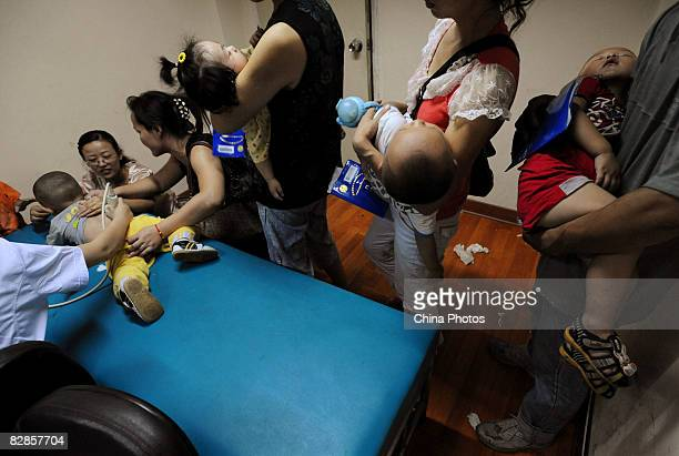 People holding babies who drank tainted milk powders queue to receive typeB ultrasonic examination in a Hospital on September 17 2008 in Wuhan of...