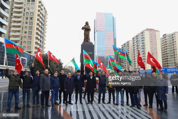 People holding banners and flags arrive to place carnations at Ana feryadi monument during the 26th anniversary of 'Khojaly Massacre' which happened...