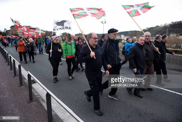 People holding Basque flags march from the Spanish Basque village of Hernani to the Martutene prison in San Sebastian during a demonstration...