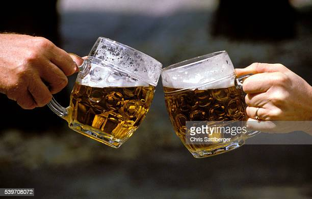 People Holding Beer Mugs and Toasting