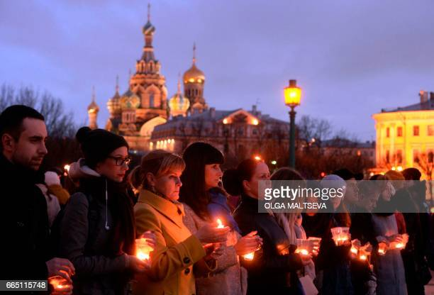 People holding candles commemorate the victims of April 3 metro train blast at The Field of Mars in Saint Petersburg on April 5 2017 / AFP PHOTO /...