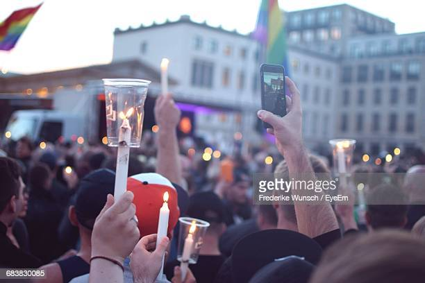 People Holding Candles On Street In City During Homage