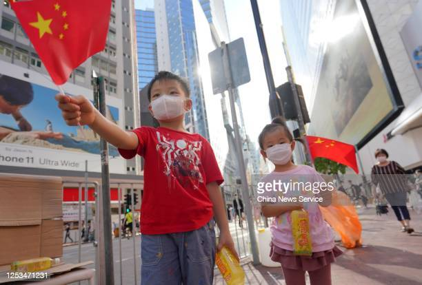 People holding Chinese flags and banners gather at Causeway Bay to show support for the newly adopted Law of the People's Republic of China on...