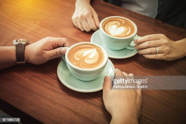People Holding Coffee Cup On Table
