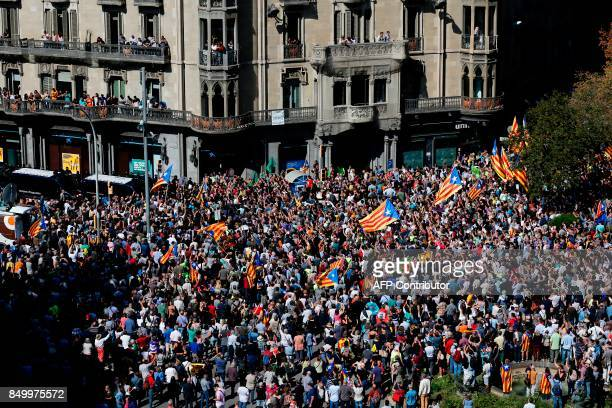 People holding 'Esteladas' attend a protest near the Economy headquarters of Catalonia's regional government in Barcelona on September 20 2017...