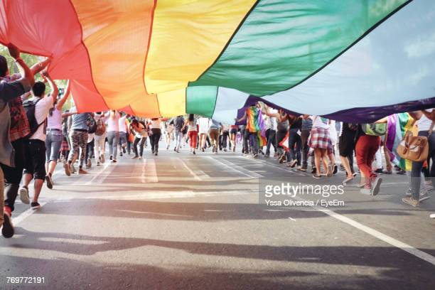 people holding flag while running on road - parade stock pictures, royalty-free photos & images