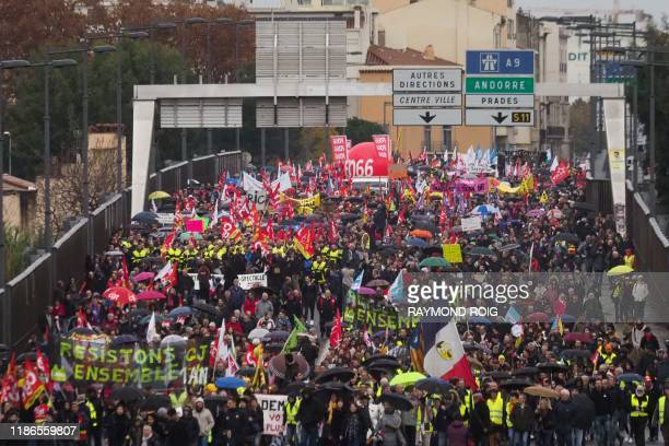 TOPSHOT People holding flags and banners take part in a demonstration to protest against the pension overhauls in Perpignan southern France on...