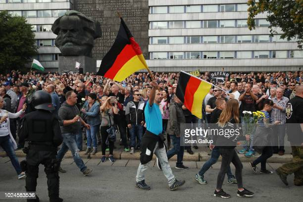 People holding German flags arrive at a right-wing protest gathering near a statue of Karl Marx the day after a man was stabbed and died of his...