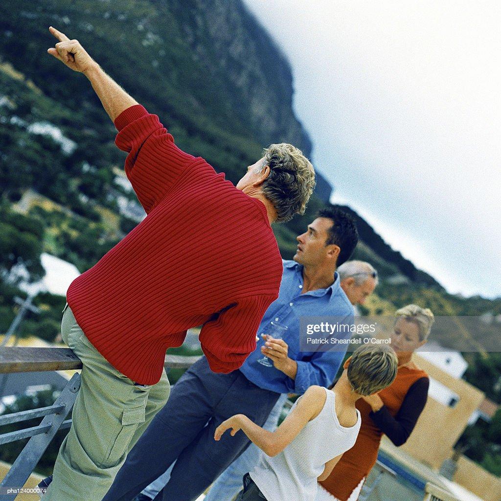 People holding glasses, man leaning on railing : Stockfoto