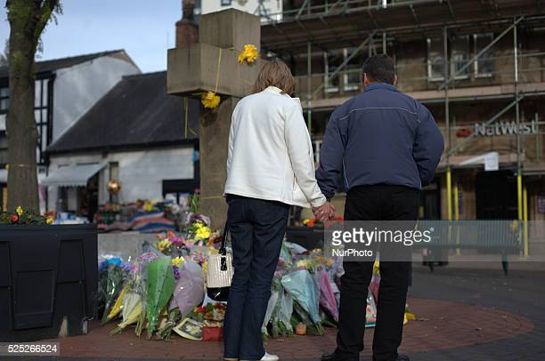 People holding hands and observiing the growing number of floral tributes at the cross in Eccles' town centre on October 5 2014 in Salford England A...