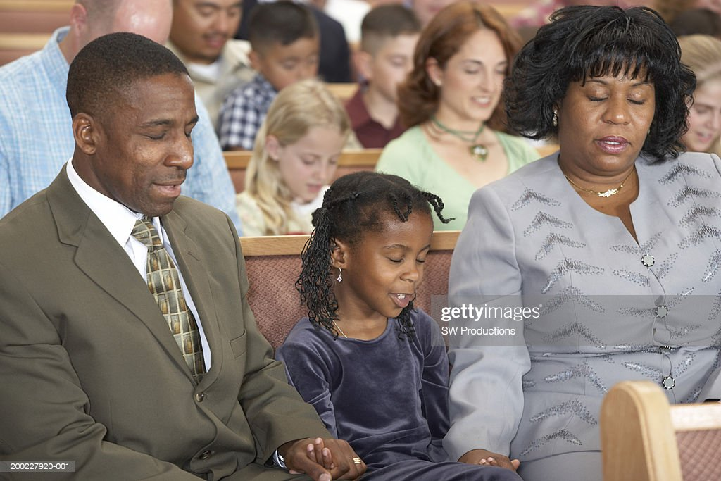People Holding Hands In Church Praying Eyes Closed Stock Photo