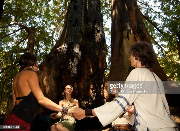people holding hands in circle in forest - naturist male stock pictures, royalty-free photos & images