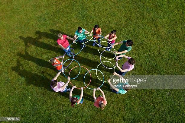 people holding hula hoops in circle - friendly match stockfoto's en -beelden
