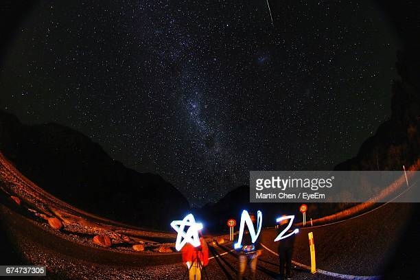 people holding illuminated alphabets against starry sky - palmerston north new zealand stock pictures, royalty-free photos & images