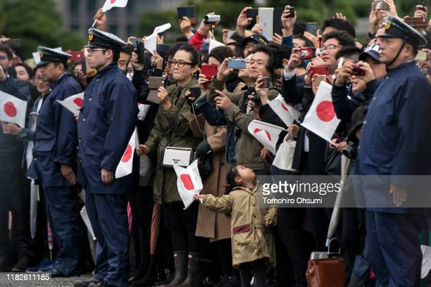 People holding Japanese national flags look at Japan's Emperor Naruhito leaving the Imperial Palace on October 22 2019 in Tokyo Japan Emperor...