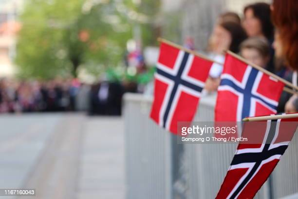 people holding norwegian flags in city - norwegian flag stock pictures, royalty-free photos & images